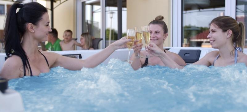 3 junge Frauen im Whirlpool trinken Sekt und prosten sich zu