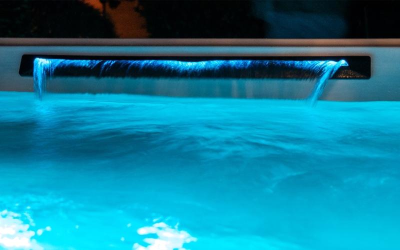 Extra breiter Wasserfall in Whirlpool, blau beleuchtetes Wasser
